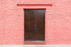 Wooden door in a pink wall Royalty Free Stock Photo