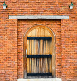 Wooden door on red brick wall background. Which closed in Stock Photos