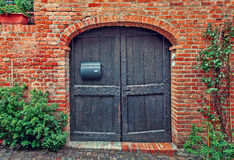 Wooden door and red brick wall. Stock Photos