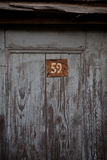 Wooden Door with Red Metal Number Royalty Free Stock Photo