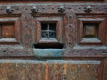 Wooden door with a rusty metal mailbox and a peephole. Stock Images