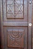 Wooden door shows Jewish symbols. A door made of wood in the israeli city of safed shows the Jewish symbols the menorah and the star of david Royalty Free Stock Photo