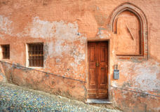 Wooden door and small paved street in Saluzzo. Stock Photos