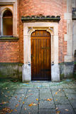 Wooden door with stone and brick wall. Wooden church door with stone surround and brick wall Stock Images