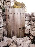 Stone fence and a wooden door. A wooden door in stone Petrela castle in the countryside of Tirana Royalty Free Stock Image