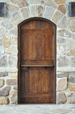 Wooden door on stone wall. A single wood door set in a natural stone wall and walkway Stock Photo