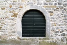 Wooden door on stone wall Royalty Free Stock Photos