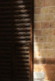 A wooden door and a stone wall, with a blade of light Royalty Free Stock Photos