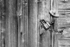 Wooden door surface with handle, old padlock, old metal and wooden latches. Wooden background and space for text. Stock Photo