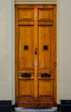 Wooden Door with Thick Black Knockers Stock Images