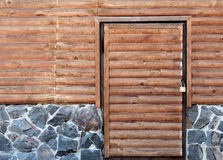 Wooden door to the utility room of a house standing on a stone foundation Royalty Free Stock Photos