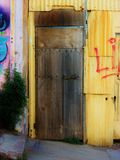 Wooden Door with Veregated Painted Metal Wall royalty free stock images