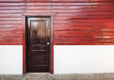 Wooden door in white and red rural house facade. Brown wooden door in white and red rural house facade Stock Image