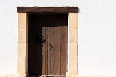 Wooden door in a white wall Royalty Free Stock Photography