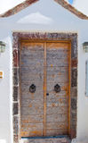 Wooden door from whitewashed house carved into the rock in Fira town on the island of Thira (Santorini), Greece. Royalty Free Stock Images