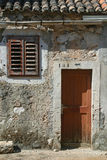 Wooden door and window. On stone wall, building facade, Pag, Croatia Royalty Free Stock Images