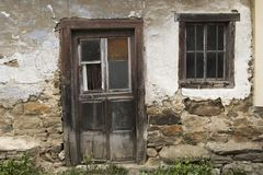 Facade of abandoned house. Wooden door, window and chipped facade belonging to an abandoned house in a village in rural Spain stock photography