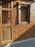 Wooden door and window of small brick cottage Royalty Free Stock Photos
