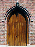 Wooden Doors. With a Gothic arch set into a brick wall. Vertical orientation Stock Image