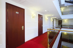 Wooden doors, red carpet on floor and handrails of balconies. In hotel Royalty Free Stock Photos