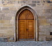 A wooden double door with pointed gothic arch in a wall made of stone blocks royalty free stock photos