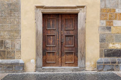 A wooden double door with rectangle door frame in a stone wall. A brown wooden door entrance to an old building. The rectangle door is weathered and aged. The Stock Images