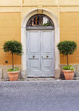 Wooden double doors with flower pots Royalty Free Stock Photo