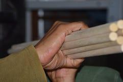 Wooden dowels bundled together. A hand holding dowels bundled together Stock Photos
