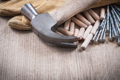 Wooden dowels claw hammer leather protective gloves and long con Stock Image