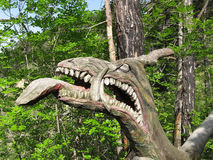 Wooden dragon head. A monster, shaped out of a tree Stock Photo