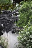Wooden Dragon head sculpture on the top of the wall in the famous Yu Garden on downtown of Shanghai. Wooden Dragon head sculpture on the top of the wall from Yu stock photography