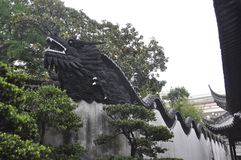 Wooden Dragon sculpture on the top of the wall in the famous Yu Garden on downtown of Shanghai. Wooden Dragon sculpture on the top of the wall from Yu Garden on royalty free stock photo