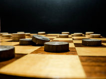 Wooden draught pieces on a wooden chessboard Royalty Free Stock Photography