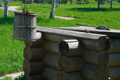 Wooden draw well with bucket. Wooden draw well in the rural area with shadoof and bucket. Green grass around it Stock Image