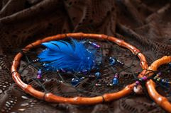 Wooden dream catcher with blue feather and multi-colored beads royalty free stock photos