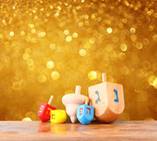 Wooden dreidels for hanukkah and glitter golden lights background.  Royalty Free Stock Photo