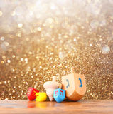Wooden dreidels for hanukkah and glitter golden lights background.  Royalty Free Stock Image