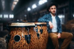 Wooden drums, closeup, male drummer on background. African wooden drums, closeup, male drummer on background. Djembe, musical percussion instrument, bongo beats Royalty Free Stock Photo