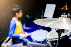 Wooden drumsticks in hands of Asian kid wearing blue and yellow t-shirts to learning and play drum set in music room royalty free stock photo