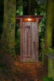 Wooden dry toilet house at night in the forest Stock Image