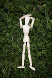 Wooden dummy. Wooden mannequin with arms laid down by the head, lying on green grass Stock Photo