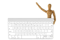 Wooden dummy with computer keyboard Royalty Free Stock Photos