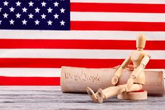 Wooden dummy and constitution of the USA. USA Constitution document, human wooden puppet with flag of United States of America behind stock images