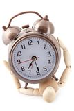 Wooden dummy crushed by old-styled alarm clock. Royalty Free Stock Photography