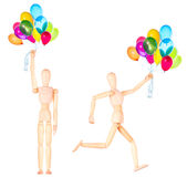 Wooden Dummy with flying balloons isolated Royalty Free Stock Image