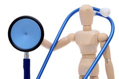 Wooden dummy hand holding stethoscope Royalty Free Stock Photos