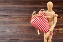 Wooden dummy holding big heart. Wooden figurine with red fabric heart and copy space. Happy Valentines Day Royalty Free Stock Photos