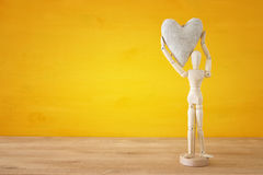 Wooden dummy holding a heart. Love, relationship and affection concept.  Royalty Free Stock Photos