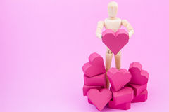 Wooden dummy holding paper box red heart shape on pink backgroun Royalty Free Stock Image