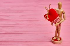 Wooden dummy holding red fabric heart. A wooden dummy figurine holding a big red heart, copy space. Happy Valentines Day Stock Images